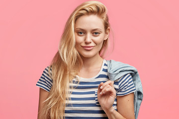 Candid shot of good looking lovely young woman with make up, dressed in sailor t shirt, holds denim jacket, looks with confident cheerful expression at camera, isolated over pink background.