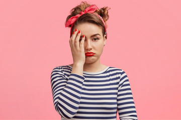 Abused offended discontent beautiful pinup girl wears striped poloneck sweater, red stylish headband, covers face with hand, pouts lips, has retro style in clothing, isolated over pink background