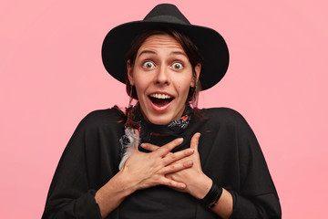 Attractive stunned Caucasian cowgirl in cowboy black outfit, looks with bated breath, being astonished to win horses races, isolated over pink background. Amazed young female in stylish hat.
