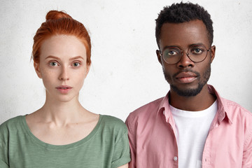 Young freckled Caucasian girl with ginger hair and her best African American friend, look directly at camera with serious expression, listen important information. Dark skinned male student in eyewear