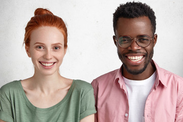 Glad mixed raced friends have broad smiles on face, happy to be invited on student`s party, celebrate successfully passed exam, isolated over concrete wall. Dark skinned man and red haired female