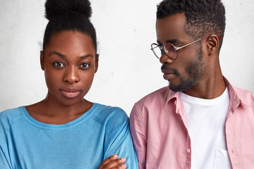 Young African couple sort out relationships. Discontent dark skinned woman looks seriously at camera, doesn`t talk with husband after quarrel, isolated over white background. Relations concept
