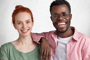 Horizontal shot of happy dark skinned male giggles and leans on girlfriend`s shoulder, glad to spend free time together, demonstrate true interracial relationship, pose against white studio background