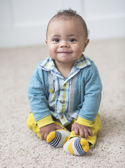 Beautiful smiling diverse baby boy portrait. Full length photo of an adorable child sitting indoors