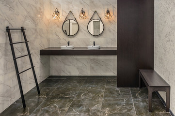 Two washbasins, two mirrors, furniture in wenge color, and three lamp in the washroom with lined with ceramic tiles