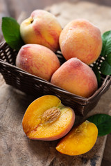 Ripe peaches in a basket and wooden, tropical fruit