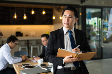 Asian businessman holding a book and pen to write a business plan. He standing and looking forward, thinking for business future and financial success.