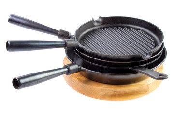 Stack of different cast iron skillets on wooden cutting board, isolated on white background