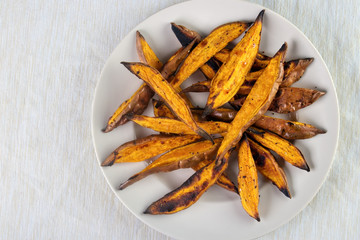 Wall Mural - Oven roasted sweet potato wedges on plate , top view