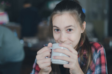 Portrait of beautiful caucasian woman holding a cup of coffee in her hand on blurred background