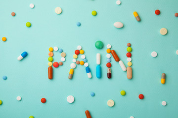 Word of pain from colored pills and capsules on a green background.