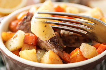 Fork and bowl with tasty meat and potatoes, close up