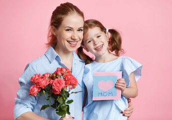 concept of mother's day. mom and child with flower on colored background