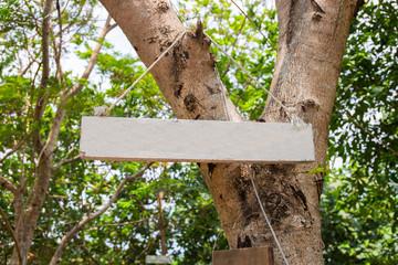 Blank wooden board on green tree. Summer park sign mockup. Empty sign on wooden board in sunny summer garden.