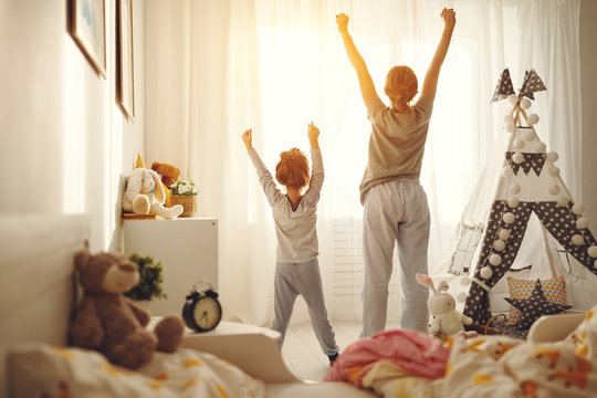 mother and child daughter stretch themselves after waking up in the morning