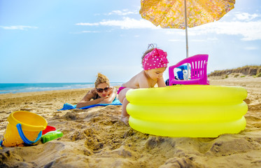 baby girl plays yellow inflatable pool mom checks her sunbathing on beach towel