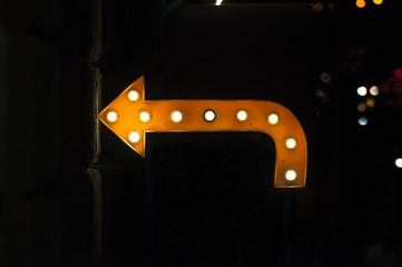 Orange arrow with light bulbs.