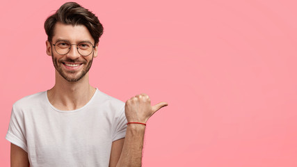 Portrait of unshaven handsome bearded young male with positive expression, wears casual white t shirt, isolated over pink studio background with blank copy space for your advertisement or text