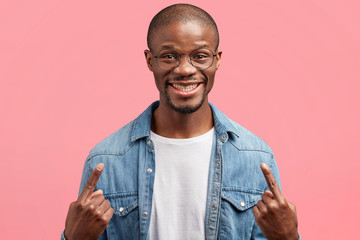 Portrait of dark skinned positive bald male, indicates at himself, being satisfied after successful shopping, demonstrates new denim jacket, poses against pink background. Mixed race glad man