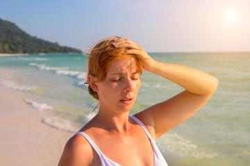 Woman having sun stroke on sunny beach. Woman on hot beach with sunstroke.