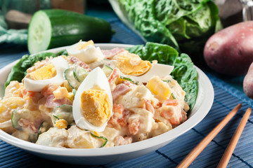 Delicious potato salad with ham, egg and cucumber
