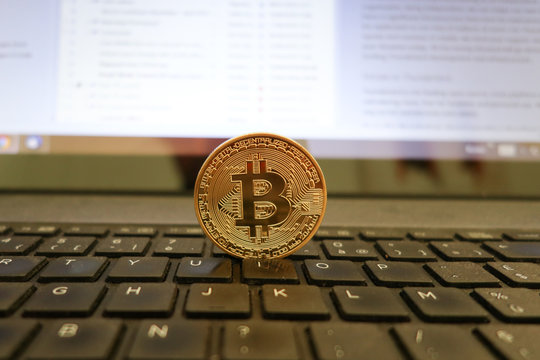 Golden bitcoin standing on computer cryptocurrency concept