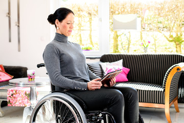 disabled woman in wheelchair with tablet PC