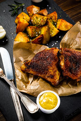 Roasted chicken legs with French fries and vegetables