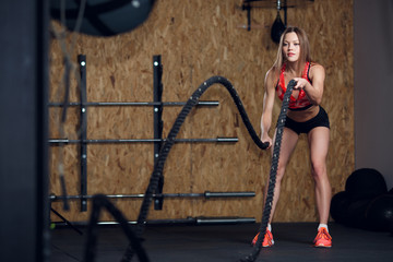 Portrait of sports woman exercising with two ropes