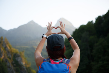 Photo from back of tourist girl with heart from palms