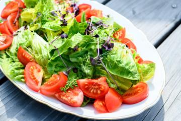 mixed summer salad on wooden ground