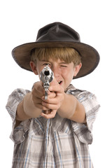 A boy pretending to be a cowboy and shooting towards camera.