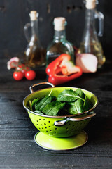 Spinach. Fresh organic spinach leaves in green metal colander. Healthy eating, vegan and diet food or dieting concept,  Dark rustic style photo.