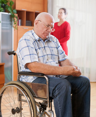 Sad elderly husband in   wheelchair and her wife