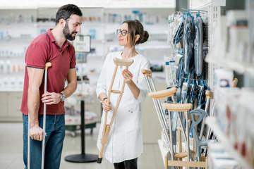 Man choosing crutches in the pharmacy