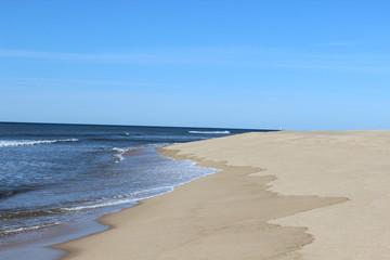 Waves crashing on isolated empty sandy coastal ocean beach