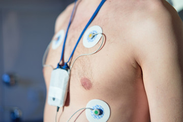 Man wearing 24 hrs electrocardiogram monitor device on his chest