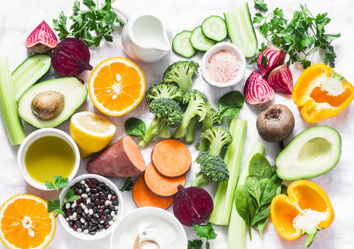 Five best vitamins for beautiful skin. Products with vitamins A, B, C, E, K - broccoli, sweet potatoes, orange, avocado, spinach, peppers, olive oil, dairy, beets, cucumber, beens. Flat lay, top view