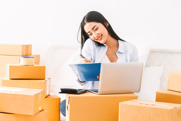 Young woman freelancer working and checklist and writing order with cardboard box on bed at home - SME business online and delivery concept