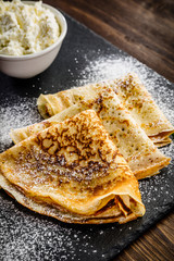Crepes with cream on wooden table