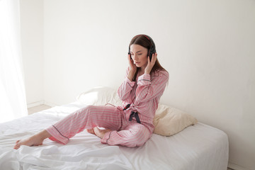 brunette in pink Pajamas listening to music with headphones on the bed