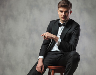 sexy gentleman dressed elegantly sitting and pointing to side