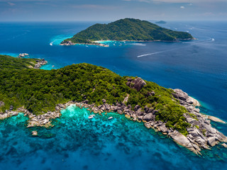 Aerial drone view of boats around the clear waters and tree covered Similan Islands in Thailand