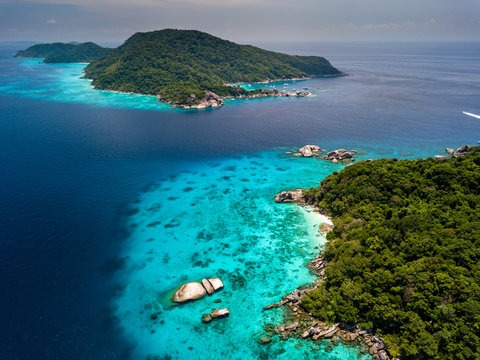Aerial view of a deserted, jungle covered tropical island with crystal clear ocean below