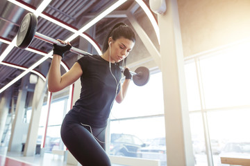 woman with barbell flexing muscles and making lunge in gym