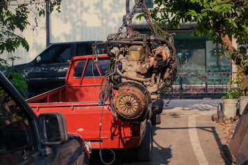 Old or used car engine hanging on the crane in the garage, Automotive industry and garage concepts.