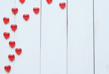 background image of red hearts on light wooden background.