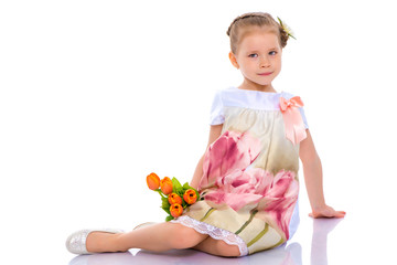 Little girl with bouquet of flowers sits on the floor.