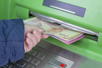 Photo of hand taking from ATM Ukrainian hryvnas