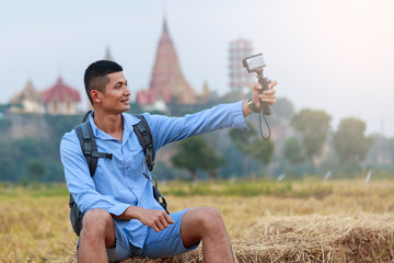 Young male tourists sit and selfie the temple in Thailand background  by video action cam. .